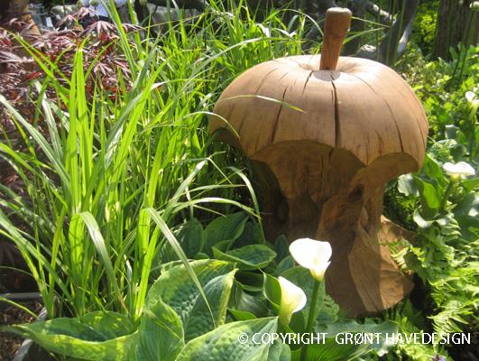 Et træskåret kæmpe æble danner dekoration i haven sammen med havens planter